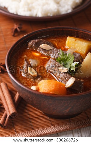 Thai beef massaman curry with peanuts close-up on the table and rice. vertical - stock photo