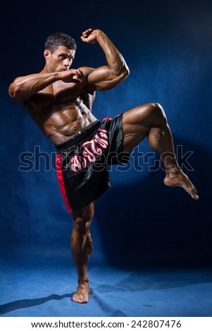 Thai boxer in full growth in a rack on a blue background. - stock photo