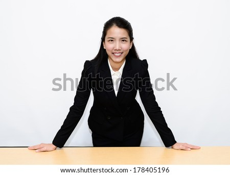 Thai Business Woman Standing put both hands on a desk - stock photo