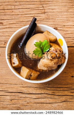 "Thai Cuisine called ""Kai Palo"" , ""Khai Palo"" or ""Pa-Lo"",  Boiled eggs with chicken drumstick and fried tofu in sweet gravy soup seasonings top with coriander. / on wood table background, food rustic. - stock photo"