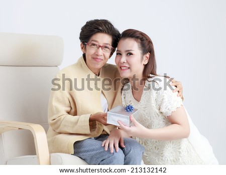 Thai daughter giving gift to mother isolated - stock photo