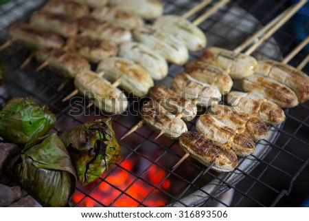 Thai dessert Grilled bananas from natural wood charcoal Snacks in Thailand Grilled sweet banana in local market   - stock photo