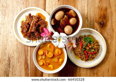 Thai Dinner set,shrimp curry,spicy pork basil,roast pork and pork stew with egg on wood background. - stock photo