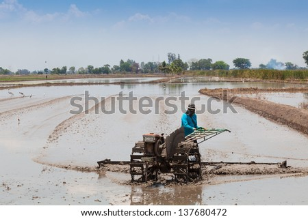 Thai farmer plowing his farm with small tractor - stock photo
