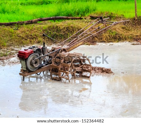 Thai farmer using walking tractors for cultivated soil for rice plantation at Thailand. - stock photo