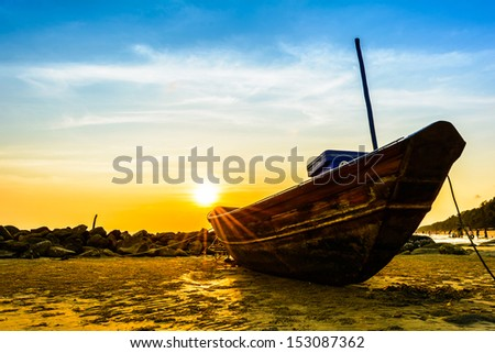 Thai fishing boat used as a vehicle for finding fish in the sea at sunset - stock photo