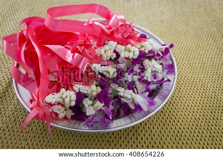 Thai Flower Garland with jasmine and orchid in Silver Tray on  yellow mat  - stock photo