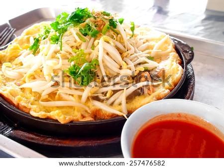Thai food, fried mussel pancake in hot pan - stock photo