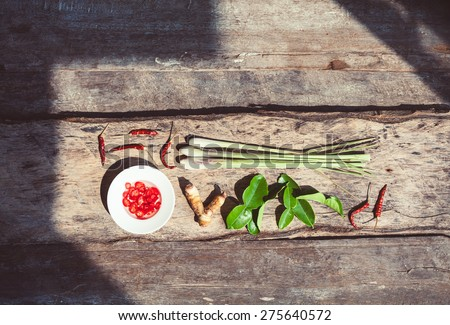 Thai food ingredients - chili pepper, lemongrass, galangal, kaffir-lime on wooden background. Aromatic asian spices.  - stock photo