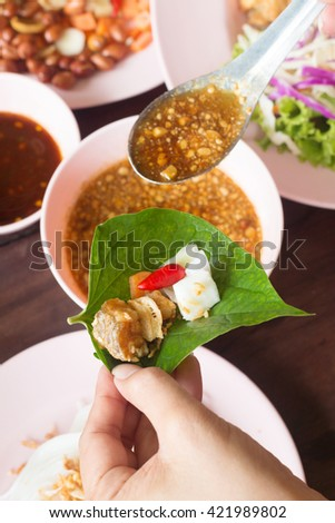 Thai Food (Miang) fried fish mix herbs wrapped in leaves. - stock photo