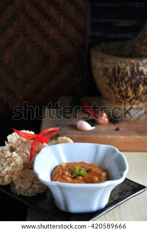 Thai food rice cracker with dipping sauce on tray with mortar on background - stock photo