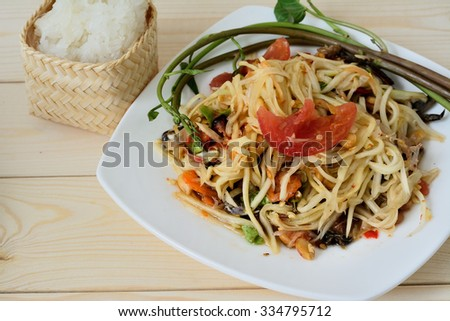 Thai food (SOMTUM) : Papaya spicy salad  with salted crab and sticky rice in wicker basket on wooden background - stock photo