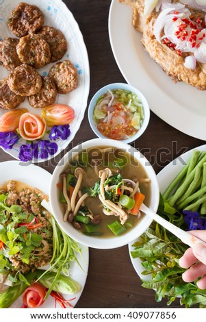 Thai Food, spicy mixed vegetable soup, spicy minced pork salad, fried fish mix herbs and local fresh vegetables. - stock photo