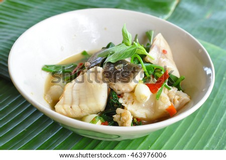 Thai food styled Steamed fillet cod fish with spicy sauce chili topping , spring onion , and sliced lemongrass and Basil leaves on top  in Thailand restaurant.