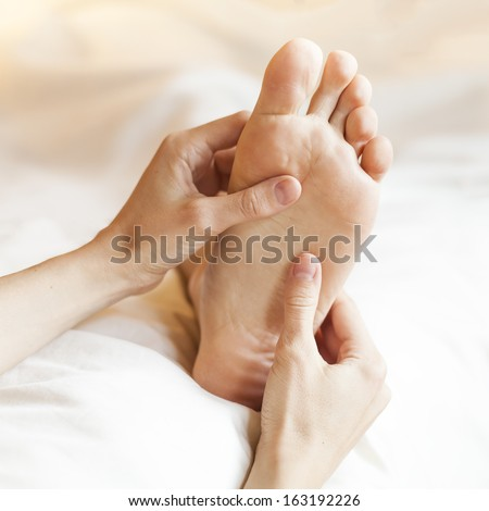 Thai foot massage with hands and thumbs - stock photo