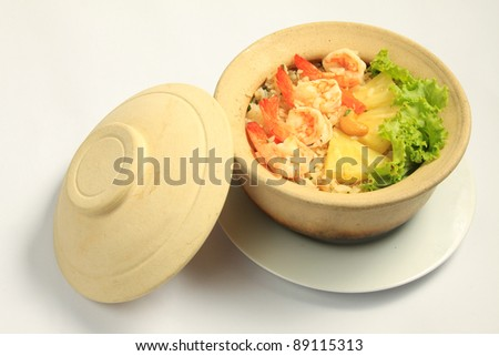 Thai fried rice with prawns and sliced pineapples baked in a pottery - stock photo