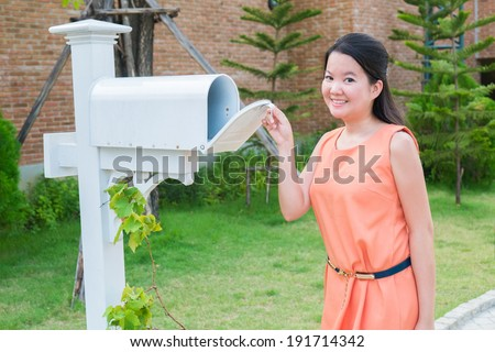 Thai girl opening mail box in the garden - stock photo