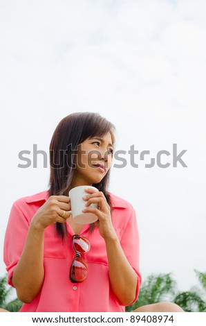 Thai happy woman drinking coffee in park