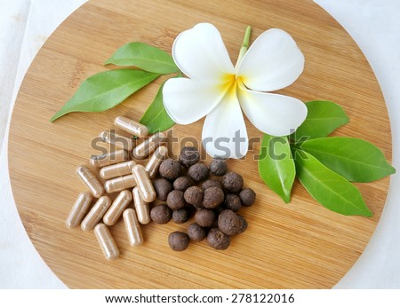 Thai herbal medicine, medicine ball lyrics Supplements in wooden tray decorated with white flower and green leaves with a white cotton background - stock photo