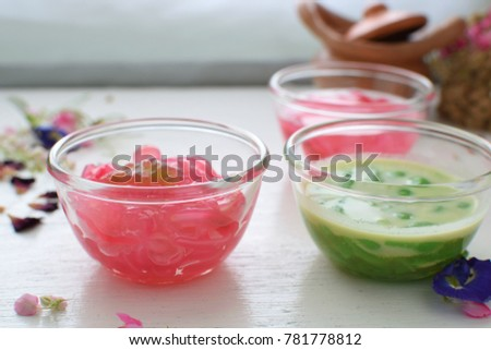 Thai jelly mixed or iced dessert (  Kanom Ruam mit )  in glass bowl  and white table.