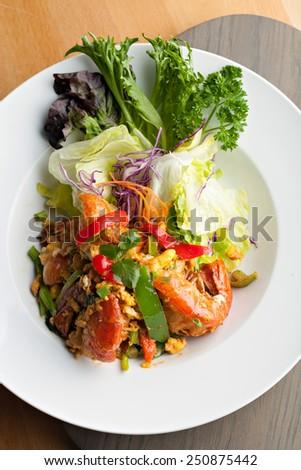 Thai jumbo shrimp salad on a round white plate. Shallow depth of field. - stock photo