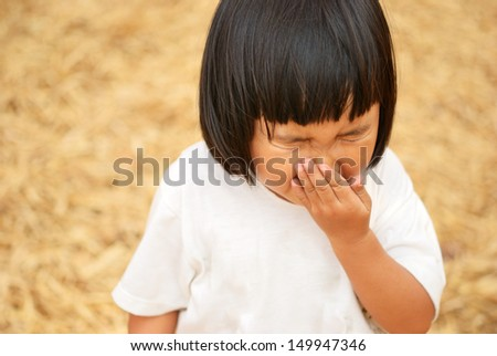 Thai kid sneezing after play in bamboo garden - stock photo