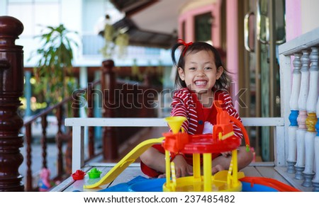 Thai little girl  playing with toys at  home.