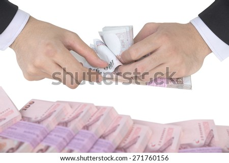 Thai Male hand counting pack of 1000 baht banknote with pile of hundred baht foreground isolated on white