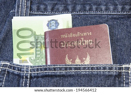 Thai passport in the back jeans pocket with euro currency - stock photo
