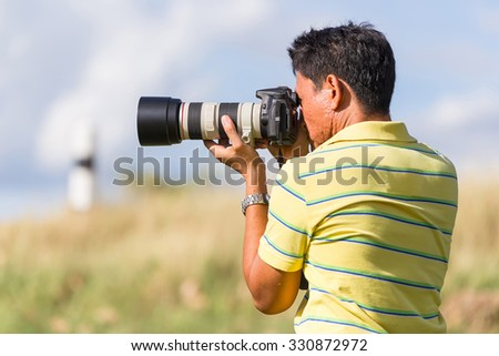 Thai photographer or traveller using a professional DSLR camera in the nature for background