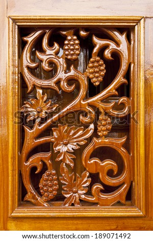 Thai plant carved pattern on lacquer wooden door - stock photo