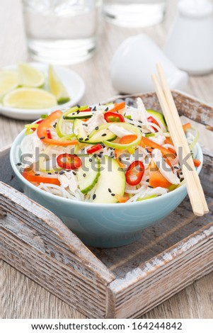 Thai salad with vegetables, rice noodles and chicken in a blue bowl, vertical - stock photo