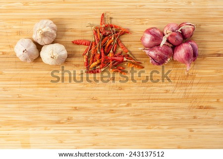 thai seasoning raw ingredient garlic red chill and onion on wood texture with stain of chop mark - stock photo