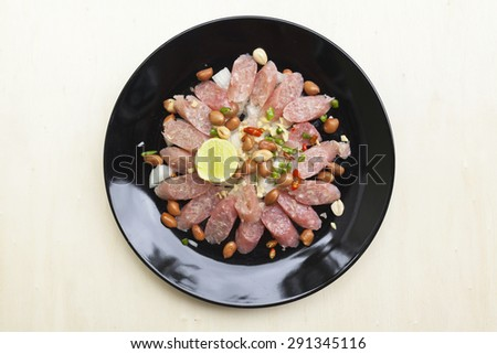 Thai sour pork sausage salad in black plate from top - stock photo