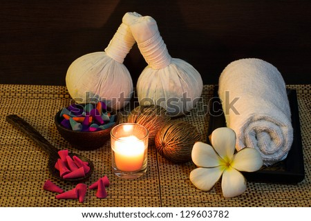 Thai spa massage setting with herbal compress balls, towel, frangipani, candle and incense cone - stock photo