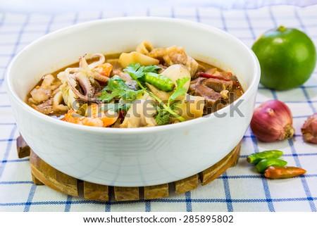 Thai spicy and sour soup (Tom yum) of shrimp, squid, pork leg and mushroom - stock photo