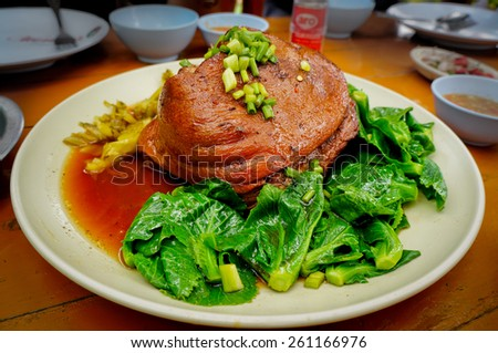 Thai stewed pork leg with vegetable in a white plate. Horizontal orientation.