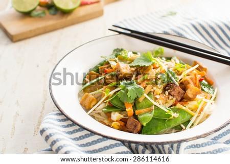 Thai stir fry: noodles with fried tofu, coriander and snow peas - stock photo