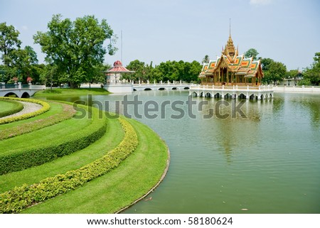 Thai style castle in the middle of pond beside green garden, Bang-Pa-In Palace, Ayutthaya Thailand - stock photo