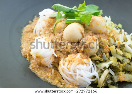 Thai style noodle eaten with curry or Thai rice vermicelli, selective focus on fishball - stock photo