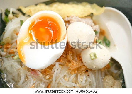 Thai style noodles with fish balls, selective focus on half boiled egg (melted yolk)