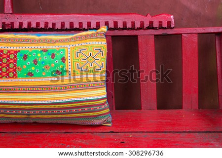 thai style pillow on red chair