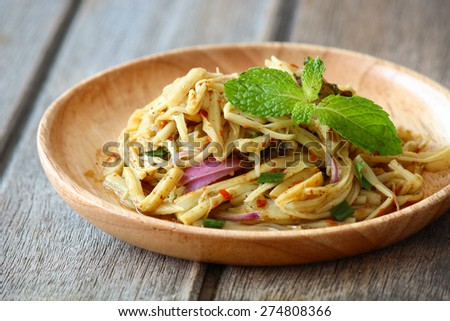 Thai style spicy bamboo pickle shoot salad on vintage wooden background