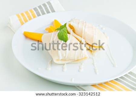 Thai style tropical dessert crepes filled with fresh mango and sticky rice. Shallow depth of field. - stock photo
