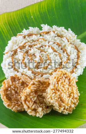 Thai Sweet Crispy Rice Cracker with Cane Sugar Drizzle on green leave background - stock photo