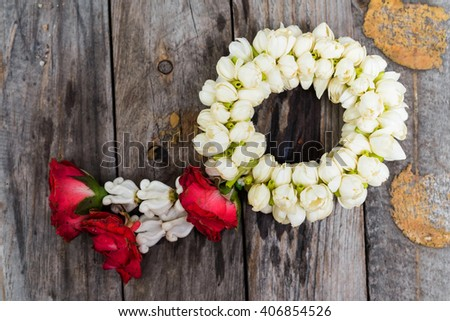 Thai Traditional garland made from Roses and jasmine on old Wooden table - stock photo