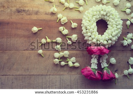 Thai traditional jasmine garland On wooden background symbol of Mother's day in thailand, to offer the monk or buddha.  - stock photo