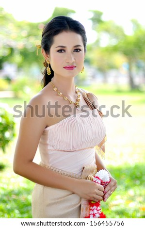 Thai woman in traditional dress in a park - stock photo