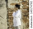Thai woman with typical welcome expression against brick background - stock photo