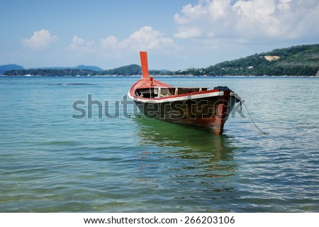 Thai wooden boat on a calm sea bay - stock photo
